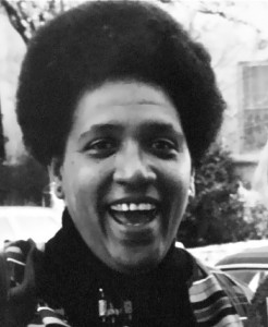 A black woman smiling broadly, she looks full of energy.