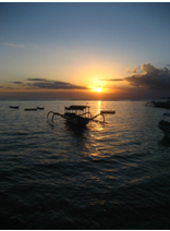 Sunset over the water, with a boat in the middle.